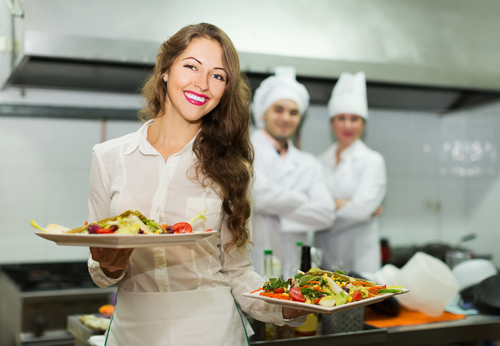 Positive waitress take plates with prepared meal at kitchen